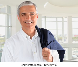 Portrait of a casually dressed mature businessman in a modern office building. Man is smiling holding his jacket over his shoulder.
