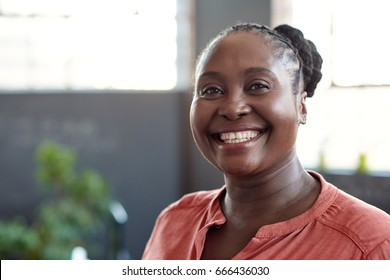 Portrait of a casually dressed young African businesswoman smiling confidently while standing alone in a bright modern office