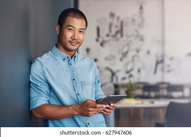 Portrait of a casually dressed young Asian designer smiling and using a digital tablet while leaning against a gray wall in a modern office