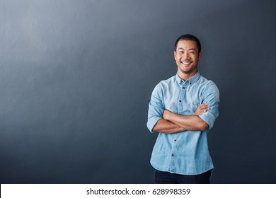 Portrait of a casually dressed young Asian designer standing confidently with his arms crossed against a gray wall in an office