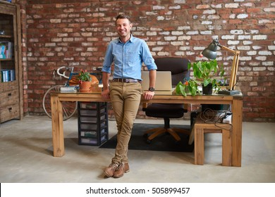 Portrait of a casually dressed young businessman leaning against a desk in a trendy brick walled office