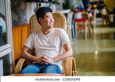 Portrait of a casually dressed young Singaporean Chinese Asian teenager boy sitting on a chair in a trendy cafe during the day. He is smiling happily as he reclines and relaxes in his seat.