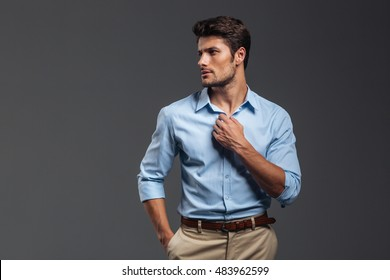 Portrait of a casualman buttoning his shirt isolated on a gray background