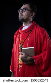 Portrait of a catholic priest  on  Black background