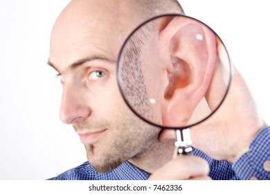A portrait of a Caucasian adult male on a white background holding a magnifying glass to his ear to indicate that he is listening.