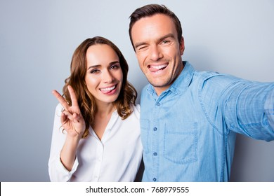 Portrait of caucasian, attractive, lovely, sweet, cute, cheerful, adult ,mature couple in shirts, making selfie on mobile phone, gesturing peace symbol, showing tongues, blinking over grey background