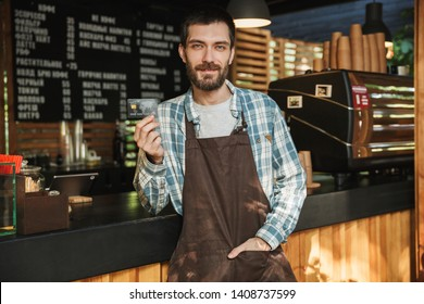 Portrait of caucasian barista man wearing apron holding credit card while working in street cafe or coffeehouse outdoor