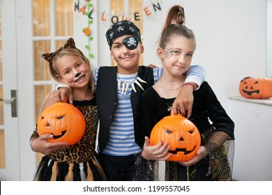 Portrait of Caucasian boy and his pretty girlfriends in beautiful Halloween costumes standing with pumpkins and smiling at camera happily
