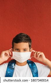 Portrait of caucasian boy of nine years old putting on surgical mask on face looking aside outdoorl. Coronavirus and school concept