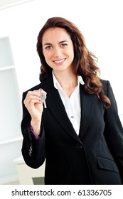 Portrait of a caucasian businesswoman holding a key against a white background