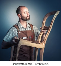 portrait of caucasian carpenter with apron and unfinished wood chair