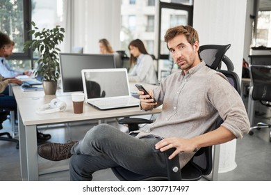 Portrait of Caucasian CEO with serious face using smart phone, sitting in office and looking at camera.