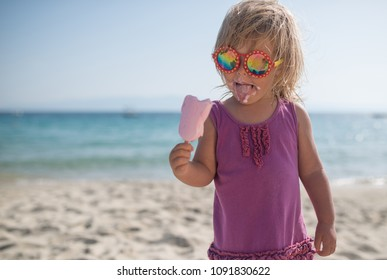 Portrait of caucasian child girl eating icecream on sandy beach