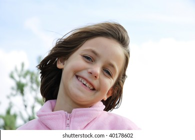 portrait of a caucasian child with a very cheesy grin showing missing teeth