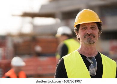 Portrait of a caucasian civil engineer wearing yellow reflective jacket and hardhat posing looking at the camera