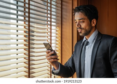 portrait of caucasian executive businesman in business suit standing by window in office using smartphone