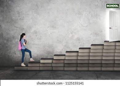 Portrait of a Caucasian female college student carrying a book while walking on book stairs toward a school door