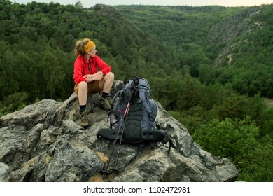 portrait of a caucasian female hiker on the rock with backpack, enjoying the view on a landscape
