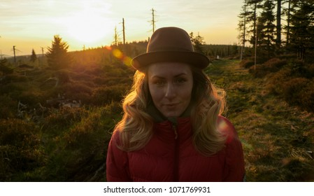portrait of a caucasian female hiker standing on a hiking trail during a beautiful sunset