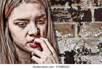 Portrait of a Caucasian Female Teenager Biting Her Fingernails in Front of a Grungy Brick Wall