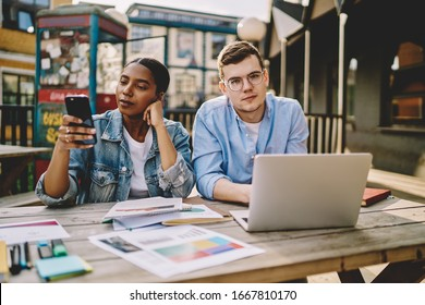 Portrait of Caucasian freelancer in optical eyewear looking at camera during brainstorming meeting with dark skinned colleague, African American woman browsing website on modern smartphone device