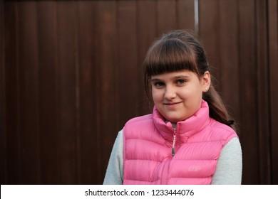 Portrait of caucasian girl in pink body warmer, wooden brown background