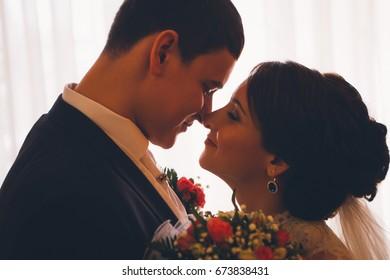 Portrait of Caucasian groom  and bride embracing