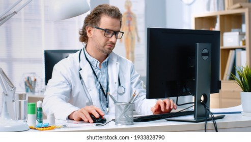 Portrait of Caucasian handsome adult experienced male physician specialist sitting at desk in cabinet checking medical documents and typing on computer in hospital, healthcare, work concept