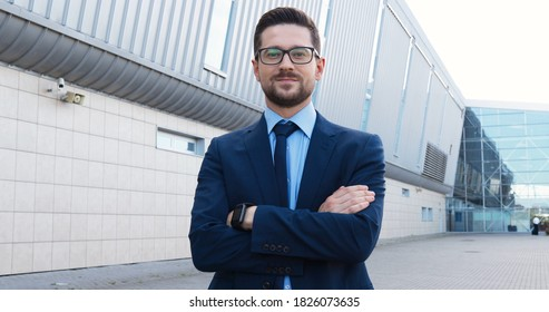 Portrait of Caucasian handsome young businessman in syut, tie and glasses standing outdoor and looking at camera. Dolly shot. Attractive man in busines style at street.