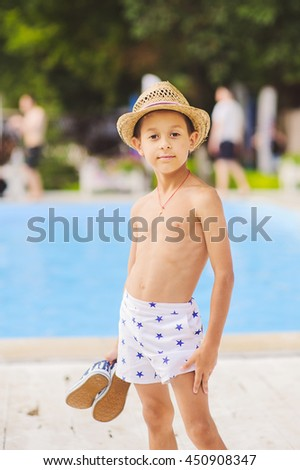 Portrait of caucasian happy baby (boy) in the straw hat near swimming pool.  Child is smiling in summer day. Kid is enjoying summer. f3bd1f6fd1c
