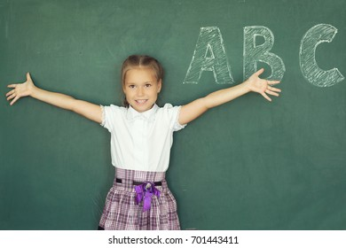 Portrait of caucasian happy child girl. School chalkboard or blackboard background. Free text copy space. Education and school concept.