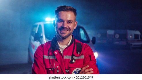 Portrait of Caucasian happy young male paramedic in red uniform smiling to camera and standing outdoor. Ambulance car on background. Attractive cherful male doctor at night shift. Call 911