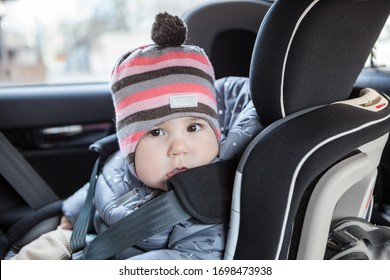Portrait of Caucasian infant child sitting in a car safety seat, eight month old