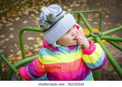 Portrait caucasian little baby girl in hat and jacket on carousel in autumn. A child looks at the sky