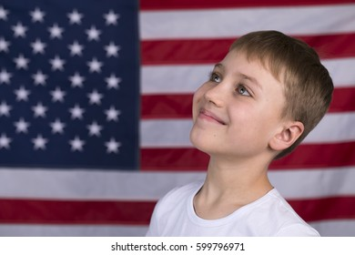Portrait of Caucasian little boy with American flag in background