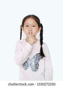 Portrait of caucasian little child girl with finger up to lips for making a quiet gesture isolated on white background. Kid showing shh sign.