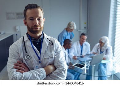 Portrait of Caucasian male doctor standing with arm crossed while diverse doctors discussing over laptop at hospital
