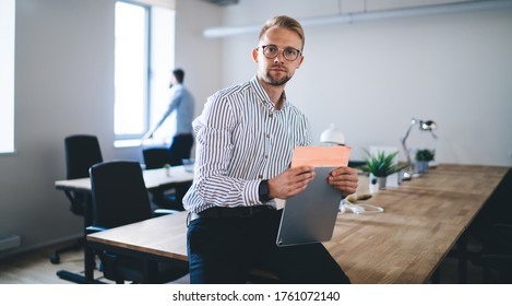 Portrait of Caucasian male entrepreneur holding modern touch pad and looking at camera during work day in company office, successful businessman in optical spectacles sitting at table desktop