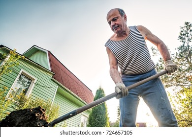 Portrait of caucasian male farmer with shovel digging the land in the country house. He is dressed in tattered trousers and a striped T-shirt