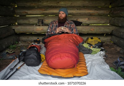 portrait of a caucasian male hiker laying on the ground in his sleeping bag