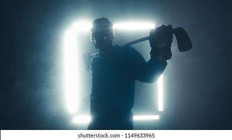 Portrait of Caucasian male ice hockey player in uniform, looking into the camera, dramatic lighting