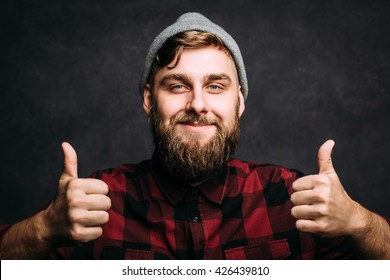 Portrait of caucasian man with big beard in checkered shirt and knitted hat. Bearded man shows thumbs up. Horizontal