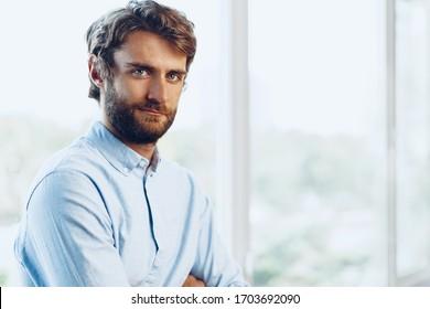 Portrait of a caucasian man in casual shirt standing near the window. Businessman portrait