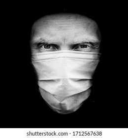 Portrait of caucasian man in medical mask to protect against COVID-19 and other viruses. Health care and self protection against COVID-19 during world pandemic. Isolated on black.