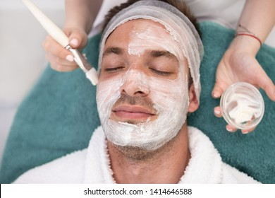 Portrait of a Caucasian man relaxing at the spa with a face mask - male beauty concepts