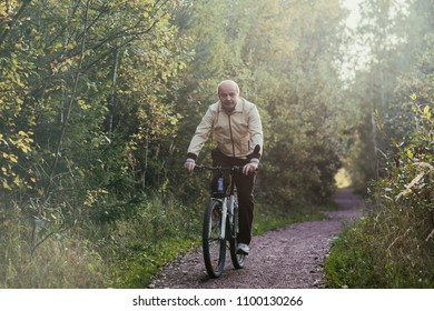 Portrait of caucasian man riding cycle in countryside