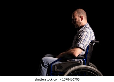 Portrait of caucasian man sitting in a wheelchair, sad and thoughtful expression. Black background. Concept of patient and physical disability.