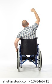 Portrait of caucasian man sitting in a wheelchair, posing with arm raised as a sign of victory. Seen from behind.