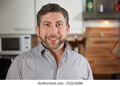 Portrait of caucasian man standing in his kitchen