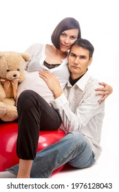 Portrait of Caucasian Man Together with Pregnant Wife Sitting On Fitball and Embracing Over White Background. Vertical Image - Shutterstock ID 1976128043
